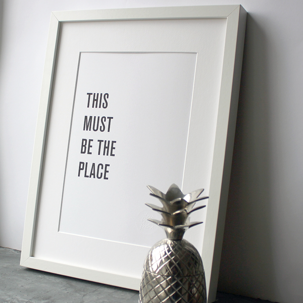 A framed print in a black and white typographic design which says 'This Must Be The Place' by Talking Heads