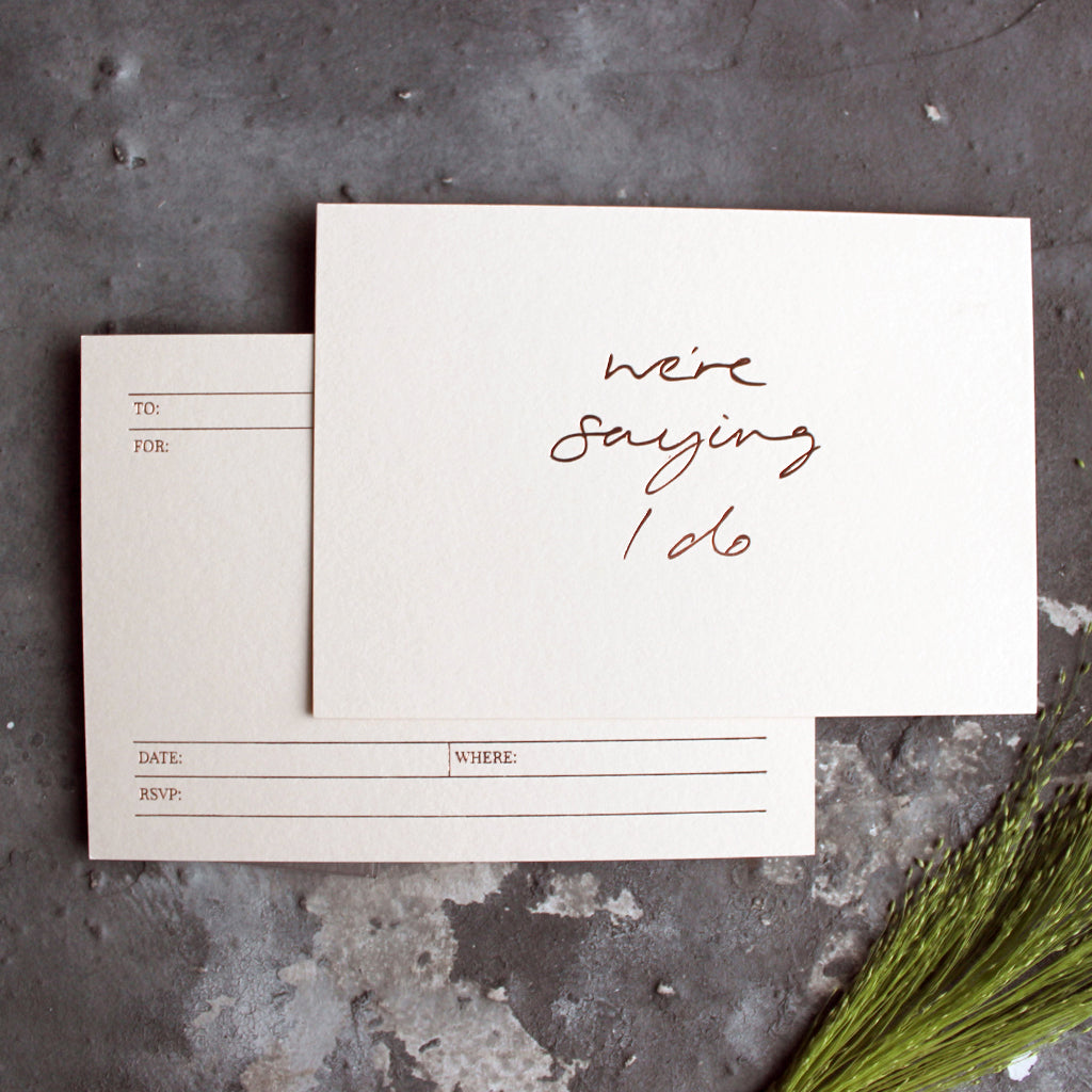 This hand foiled save the date invitation says 'We're Saying I Do' and is available on white, blush or pale grey luxury paper