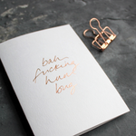 This white christmas card has 'Bah Fucking Hum Bug' handprinted in rose gold foil in handwriting on the front.