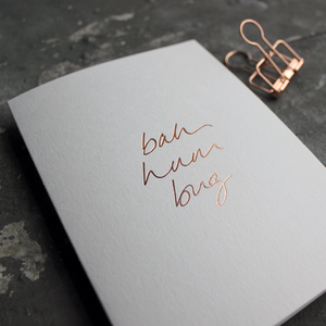 This white christmas card has 'Bah Hum Bug' handprinted in rose gold foil in handwriting on the front.