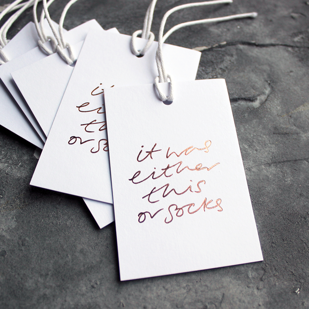 "Luxury white gift tags with waxed cotton thread have ""It Was Either This Or Socks' handprinted in handwritten rose gold foil."