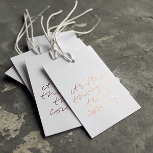 "Luxury white gift tags with waxed cotton thread have ""It's The Thought That Counts' handprinted in handwritten rose gold foil."