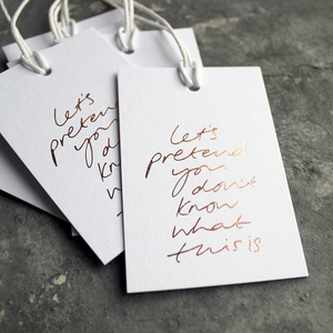 "Luxury white gift tags with waxed cotton thread have ""Let's Pretend You Don't Know What This Is' handprinted in handwritten rose gold foil."