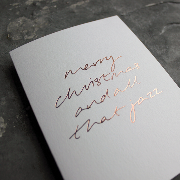 This white christmas card has 'Merry Christmas And All That Jazz' handprinted in rose gold foil in handwriting on the front.