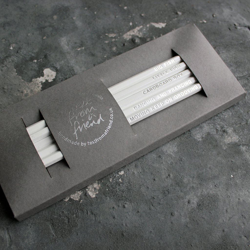 White HB pencils printed with silver foil phrases and packaged in a grey paper box.