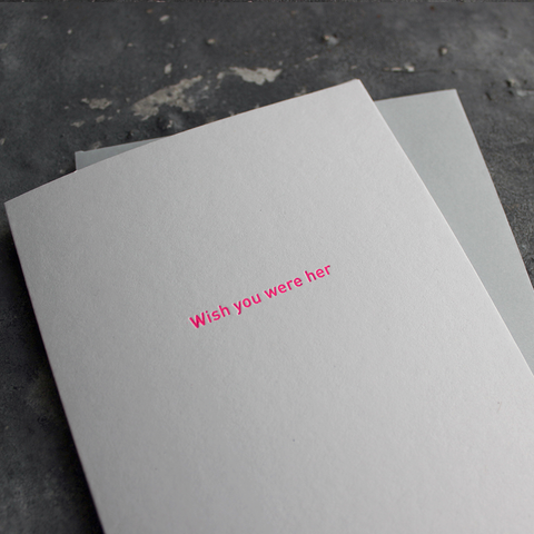 The front of the card says Wish You Were Her and is stamped in neon pink foil on a pale grey card