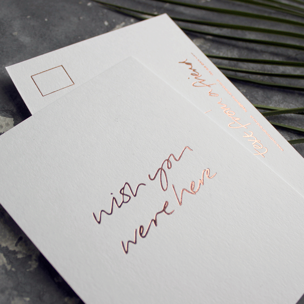 a hand pressed rose gold foil postcard that says Wish You Were Here