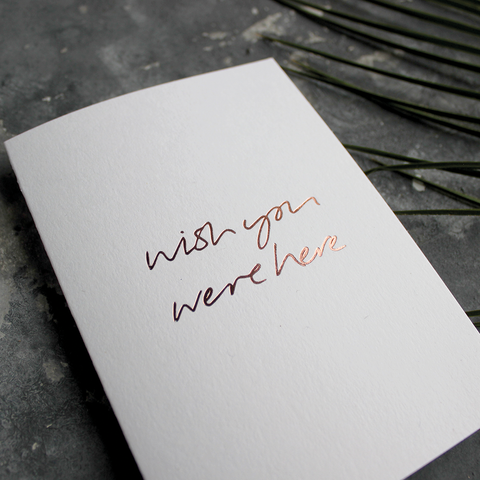 The front of the card says Wish You Were Here hand foiled in Rose Gold
