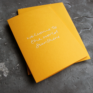 This yellow new baby card says Welcome To The World sunshine in white foil.