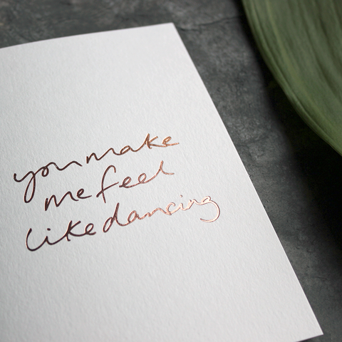 the handwritten words 'you make me feel like dancing' are hand foiled in rose gold on the front of the card
