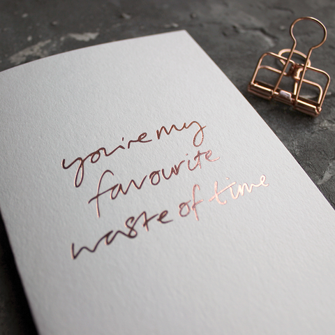 the front of the card says You're My Favourite Waste Of Time handwritten and hand pressed in rose gold foil