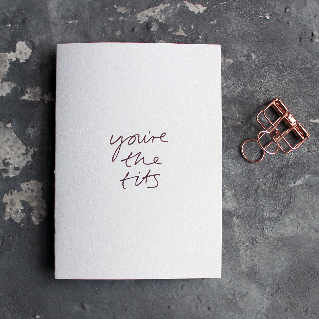 The front of the white card says You're The Tits and is hand pressed in rose gold foil