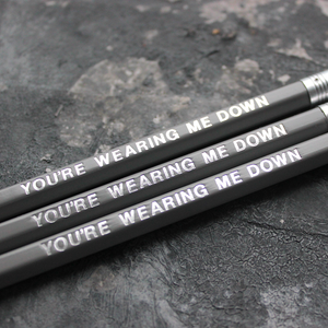 Grey pencils with a silver foil blocked message that says You're Wearing Me Down