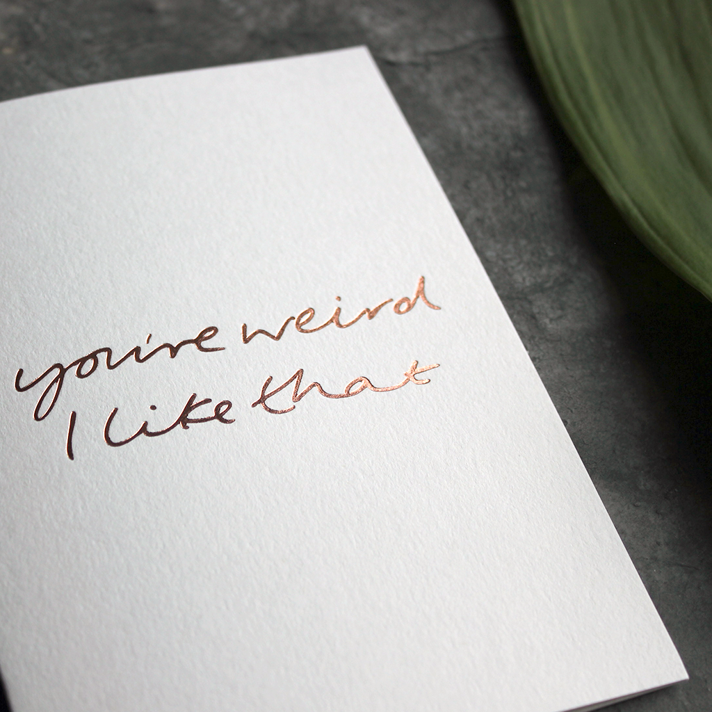 this luxury card says 'you're weird i like that' and is handwritten and hand printed in rose gold foil