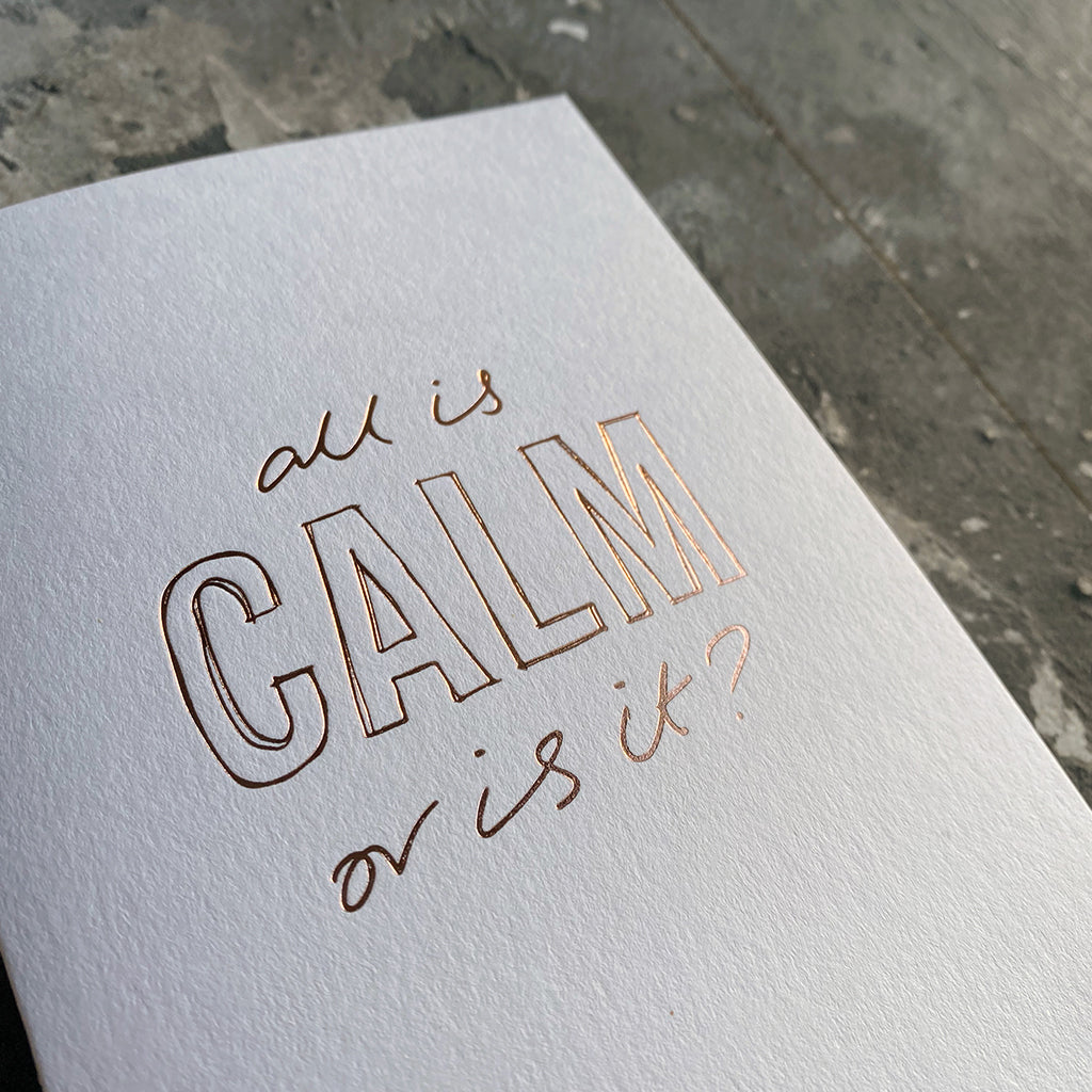 This luxury Christmas Card has a hand written rose gold foil block message saying All Is Calm Or Is It? on the front