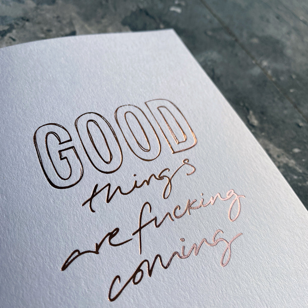 This luxury Christmas Card has a hand written rose gold foil block message saying Good Things Are Fucking Coming on the front