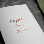 A rose gold hand foiled card saying Happily Ever After