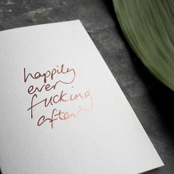 A rose gold handfoiled card saying Happily Ever Fucking After