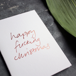 Happy Fucking Christmas card is handwritten in rose gold foil blocking on white card