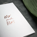 this luxury wedding card that's handwritten with a rose gold foil message saying mr and mrs