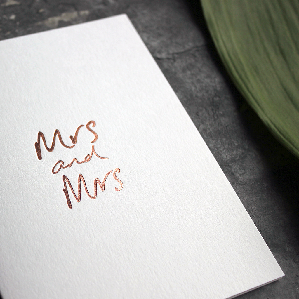 this luxury wedding card for the gay couple says Mrs and Mrs on the front, handwritten and hand foiled in rose gold