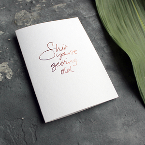 A birthday card with the message 'Shit you're getting old' hand written and hand foiled in rose gold