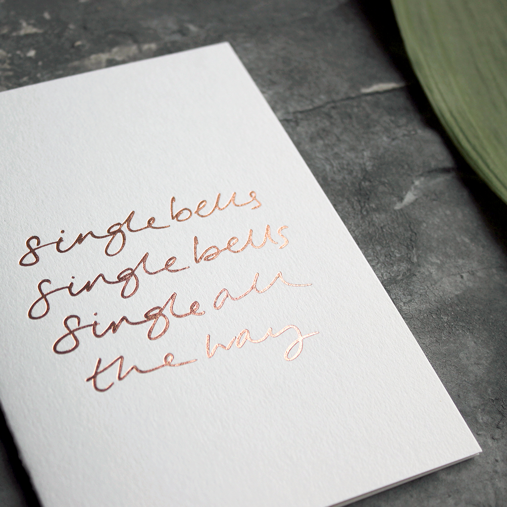 a rose gold foil christmas card says single bells single bells single all the way on the front