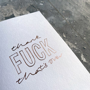 This luxury Christmas Card has a hand written rose gold foil block message saying Thank Fuck That's Over on the front