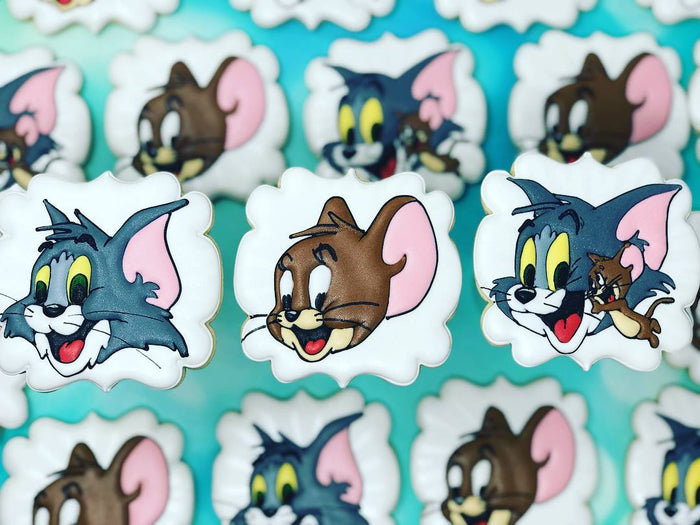 Tom And Jerry Birthday Party Iced Sugar Cookies by @creativeconfectionsbyshannon featured on TheIcedSugarCookie.com #tomandjerrycookies #tomandjerry #decoratedcookies #royalicingcookies #theicedsugarcookie #tomandjerryparty #partyideas #cookies #sugarcook