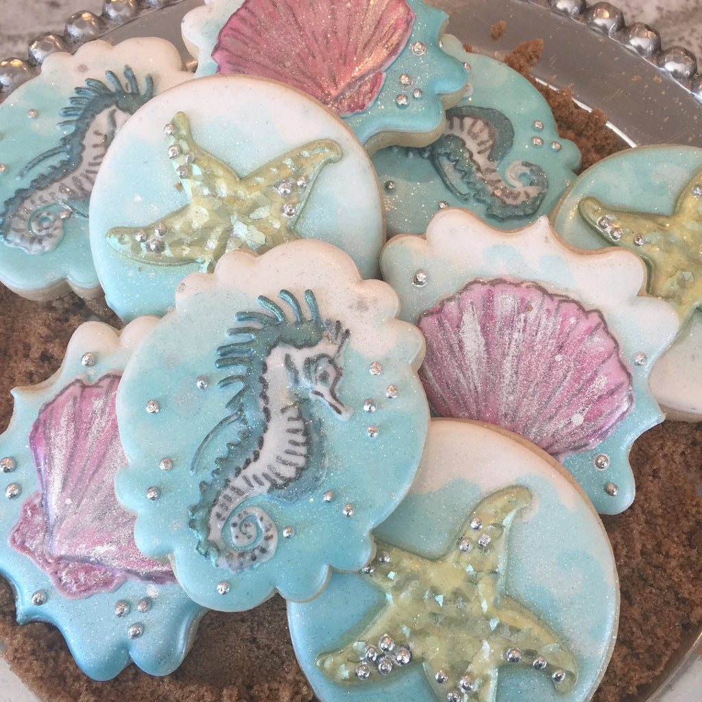 "Beach Themed Iced Sugar Cookies created by ""Frosted Sweet Peas"" featured on TheIcedSugarCookie.com #cookies #sugarcookies #decoratedcookies #beachcookies #seahorsecookies #starfishcookies #seashellscookies"