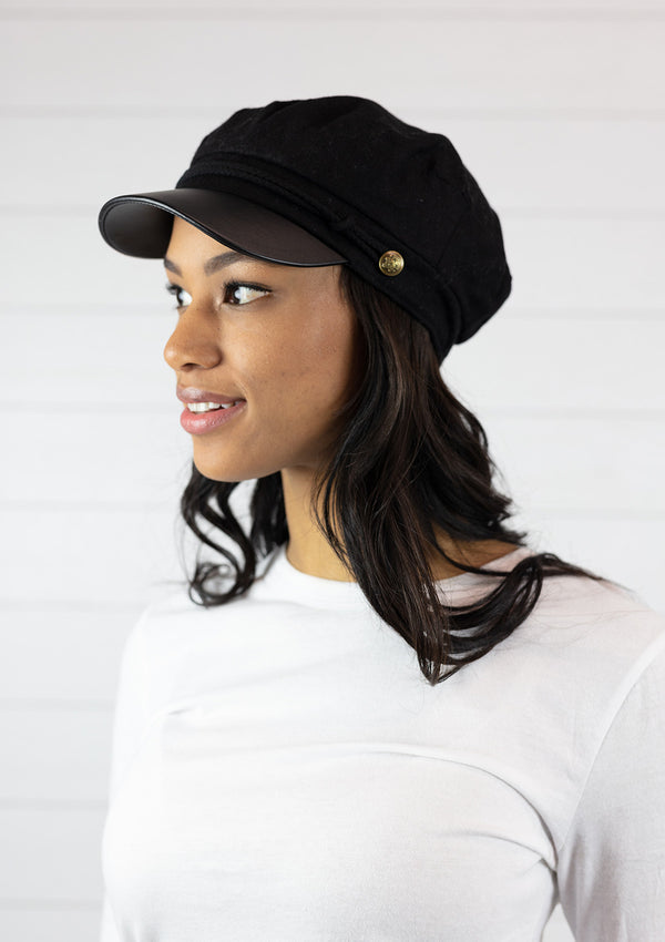 Woman wearing faux leather fisherman's cabbie hat in black