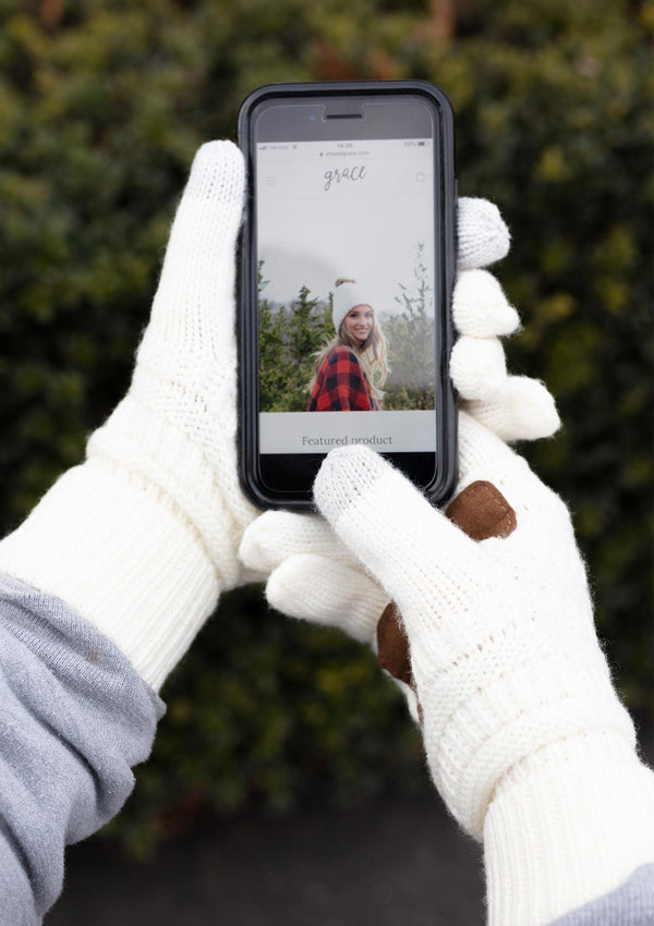 Woman wearing white knit gloves with a suede palm holding an iphone