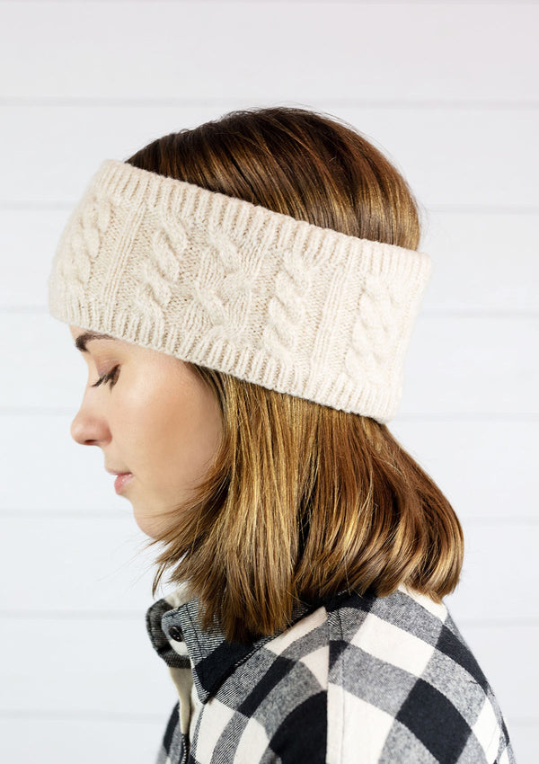 Woman wearing a cream colored cable knit fleece lined headband