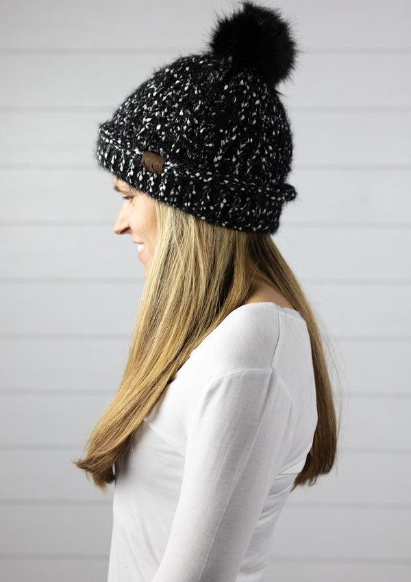 Woman wearing a super soft tweed confetti knit beanie winter hat with faux fur pom pom
