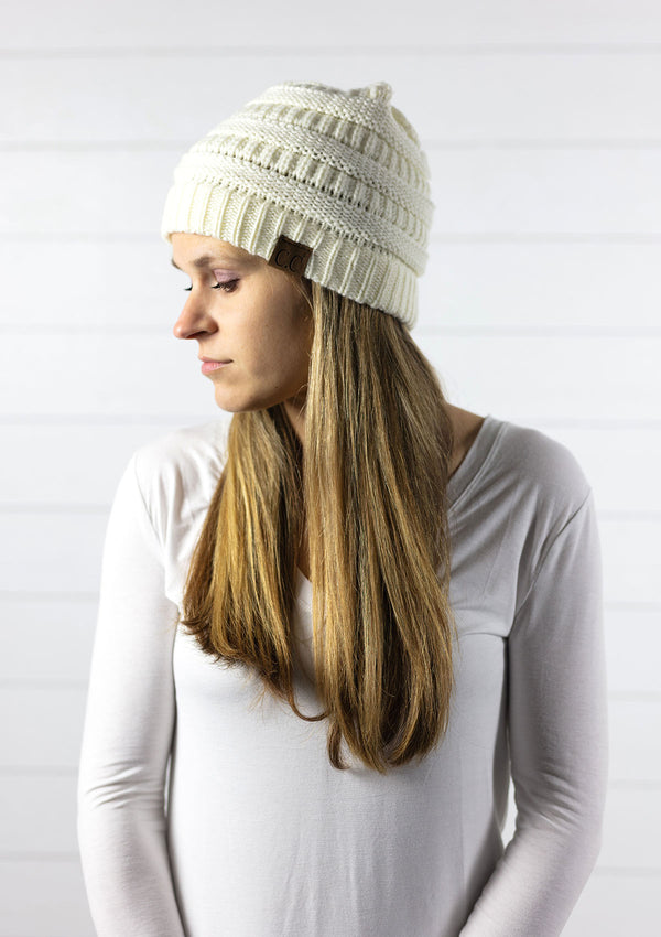 woman wearing a classic knit winter beanie hat in an ivory color