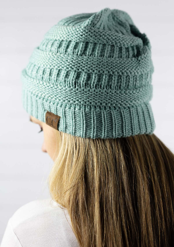 woman wearing a classic knit winter beanie hat in a mint color