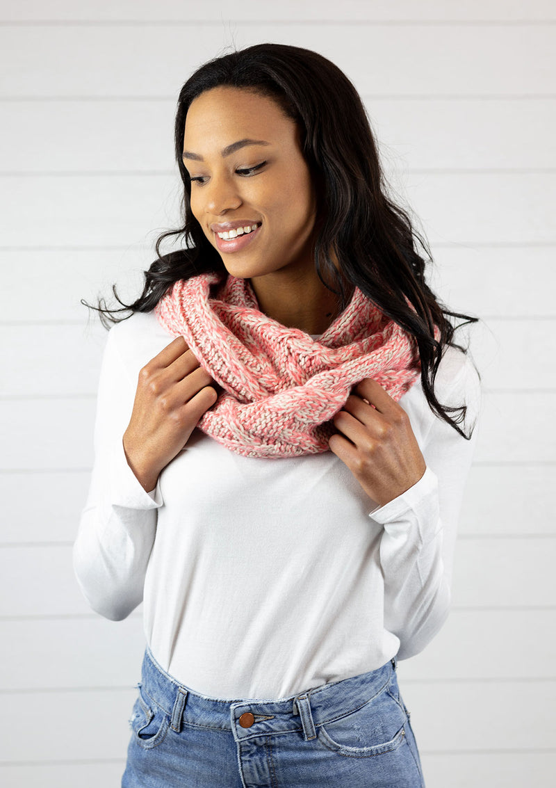 Woman wearing a nordic infinity scarf in coral.