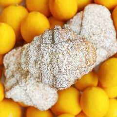 Meyer Lemon Almond Croissant covered in powdered sugar  with Meyer lemons in background