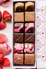 Ginger Elizabeth Mother's Day 12 piece Chocolate bonbon box shown from above with edge of Mom box sleeve, strawberries, candied rose petals and raspberries.close up