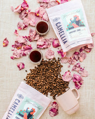 Rose Coffee bags shown with mugs of coffee, beans and candied rose petals