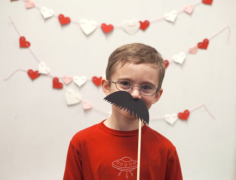 Mr6 sporting a handmade mustache photo prop at the photo booth at his school's Valentine's Day party