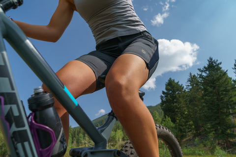 Women with water bottle on her mountain bike, wearing Elevenpine Rip it Up shorts.