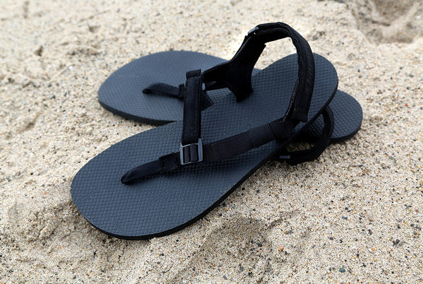 Black Chargers sandals on sand
