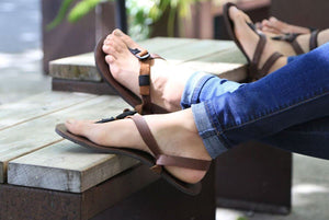 Feet relaxing in Shamma All Browns sandals on bench