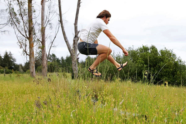 Shamma Chargers sandals leaping in the air over grass