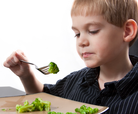 Boy ponders eating broccoli