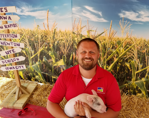 Pinnaclife Pharmacist Kyle Holding a Pig on RAGBRAI in Jefferson Iowa