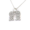 Side angle view of sterling silver pendant necklace with twin characters next to each other.