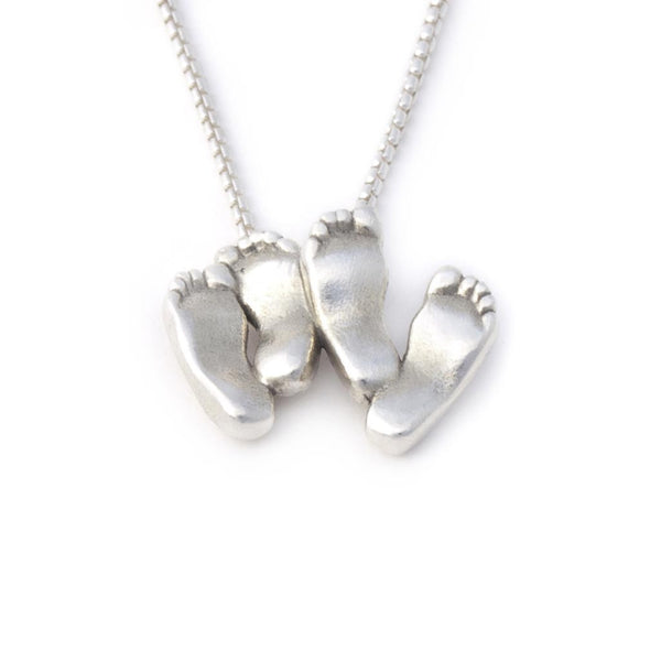 Close up view of Sterling silver twin baby's feet pendant.