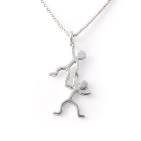 Straight on view of Sterling silver pendant with twins figurines hanging on to each other dangling from the necklace.